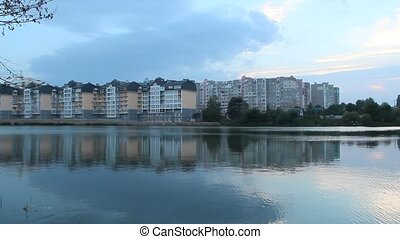Multistory modern house on lake bank. Block house near river in evening
