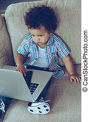 Multitasking baby. High angle view of little African baby boy using his laptop and smartphone while sitting on the couch at home