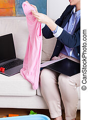 Multitasking woman working at home and folding laundry -...