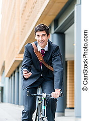 Multitasking young businessman riding a bicycle to work