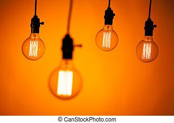multitud, de, bombilla, lámparas, en, fondo anaranjado