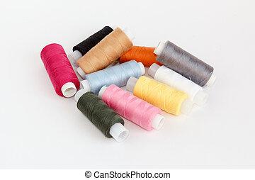 Multy coloured bobbins of thread on white