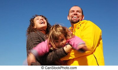 mum and daddy shakes daughter on hands and all of them smile against clear sky
