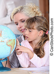 Mum and daughter looking at a globe