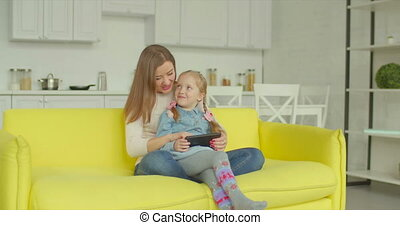 Mum and daughter with tablet pc browsing online - Cheerful...