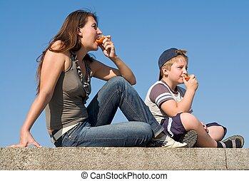 Mum and son eat peaches