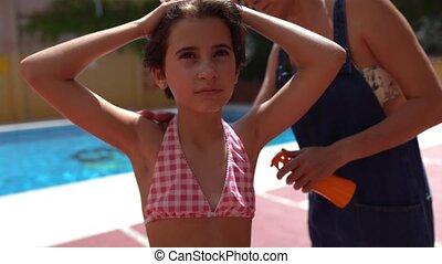 Mum applies sunscreen to her daughter. Mother putting sunscreen on her little girl's shoulders