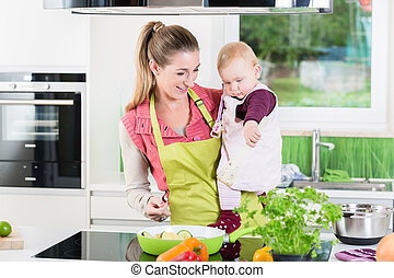 Mum cooking with baby in arm