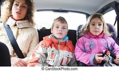 mum, daughter and son sit on back seat of moving car and talk