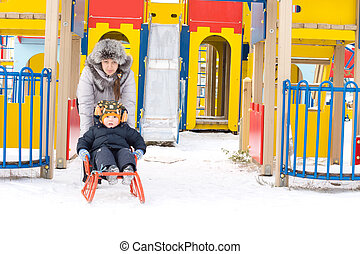 Mum giving her young son a toboggan ride