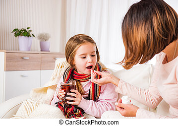 Mum giving pill to ill daughter