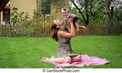 Mum holds baby - Mum holds on hands of her little daughter...
