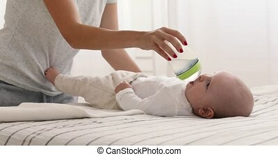 Mum is feeding the baby with water bottle