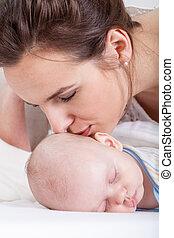 Mum kissing her newborn baby