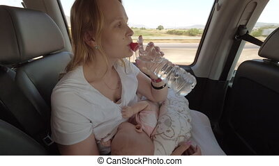 Mum nursing baby and drinking water in moving car