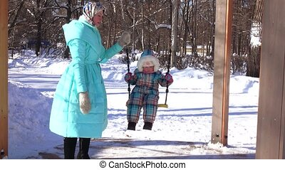 Mum on skates and daughter on sled