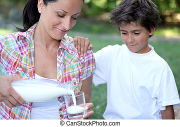 Mum pouring out a glass of milk for her son