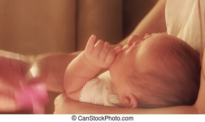 Mum soothing her fussy newborn baby with the pink pacifier -...