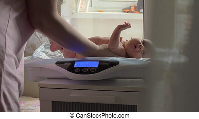 Mum weighing baby with electronic scales