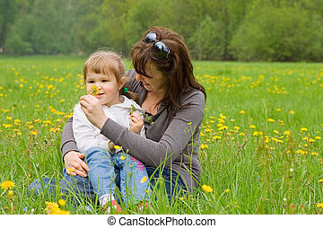 Mum with a daughter collect dandelions