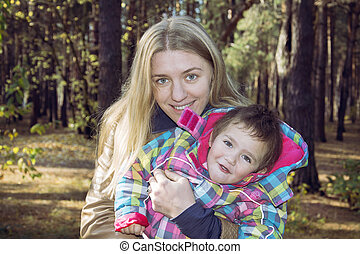 Mum with a daughter in autumn forest.
