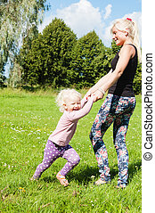 Mum with a daughter play to a glade