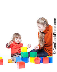 Mum with a small daughter cubes, studio shooting play