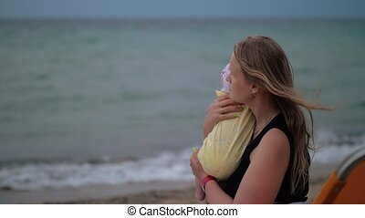 Mum with baby looking the sea - Slow motion shot of a young...