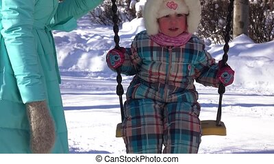 Mum with daughter on swing in a winter park