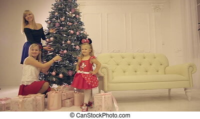 Mum with daughters decorate the Christmas tree in the new year eve