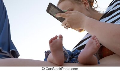 Mum with sleeping baby at the beach. Woman using cellphone