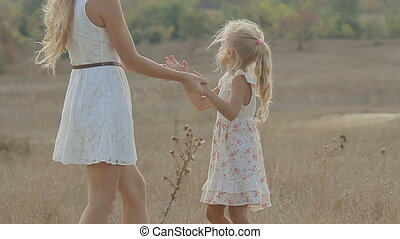 Mum with small daughter laughing and having fun in the middle of the field, mother daughter turns