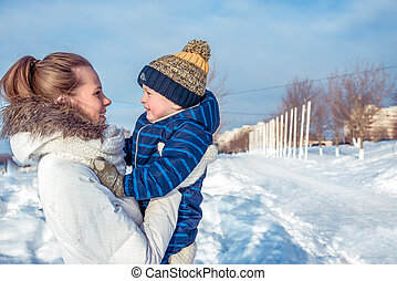 Mum with the small son of 3 years, in sunny day in a city in the winter. Free space for text. Happy smiling relaxing in nature. Happy family in the fresh air.