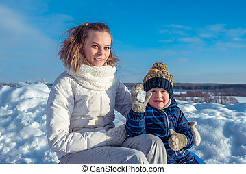Mum with the small son of 3 years, in sunny day in a city in the winter. Play snowballs. Happy smiling relaxing in nature. Happy family in the fresh air.