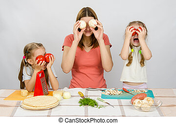 Mum with two little girls having fun at the kitchen table playing with vegetables