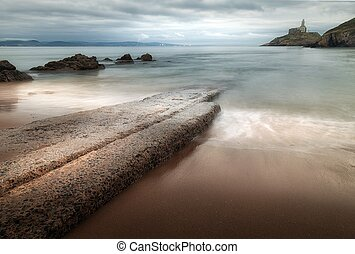 Dusk at the old concrete slipway at Mumbles beach and lighthouse, Swansea, South Wales, UK