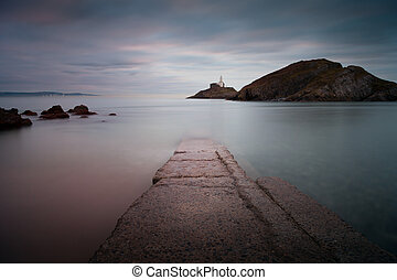 The old concrete slipway at Mumbles beach and lighthouse