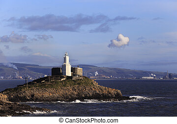 Mumbles Head lighthouse with the industrial chimneys of Port Talbot visible on the other side of Swansea Bay