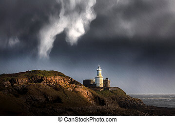 Stormy weather and rain over Mumbles lighthouse on Swansea Bay, South Wales, UK