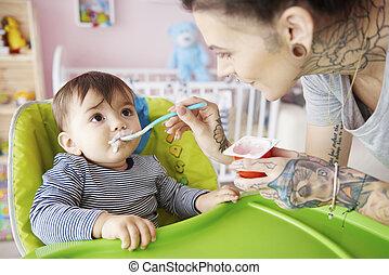Mummy feeding boy with yoghurt