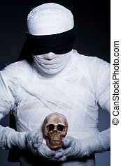 Mummy with skull in dark room