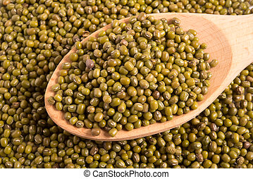 Mung beans in a wooden spoon on mung beans background
