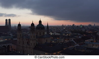 Munich at Night Time with view of Theatinerkirche Cathedral and City lights at Dusk after Sunset, Aerial Dolly slide right 4K