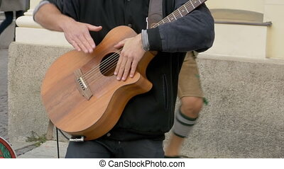 Street musician playing on acoustic guitar. Slow Motion
