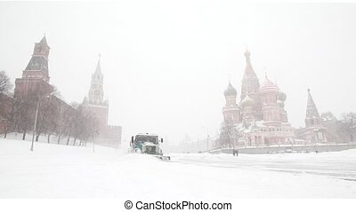 municipal units move near Moscow Kremlin and Saint Basil's Cathedral and remove snowfall with plows
