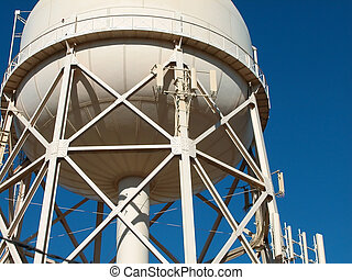 A municipal water tank showing the steel beam construction of its support tower shot against a clear blue sky