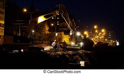 Municipal works at night, excavator removing emergency ...