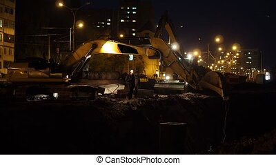 Municipal works at night, excavator removing emergency communication wreck