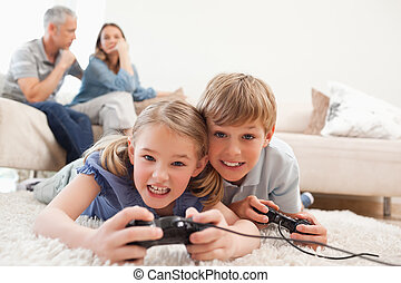 muntre, børn spille, boldspil video, hos, deres, forældre, på, den, baggrund, ind, en, leve rum
