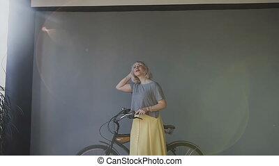mur, taches rousseur, regarde, blonds, portrait, girl, robe, désinvolte, dehors, debout, vivant, conduite, vélo, fenêtre., agréable, femme, room., bike., éclairage, fond, gris, elle, grand